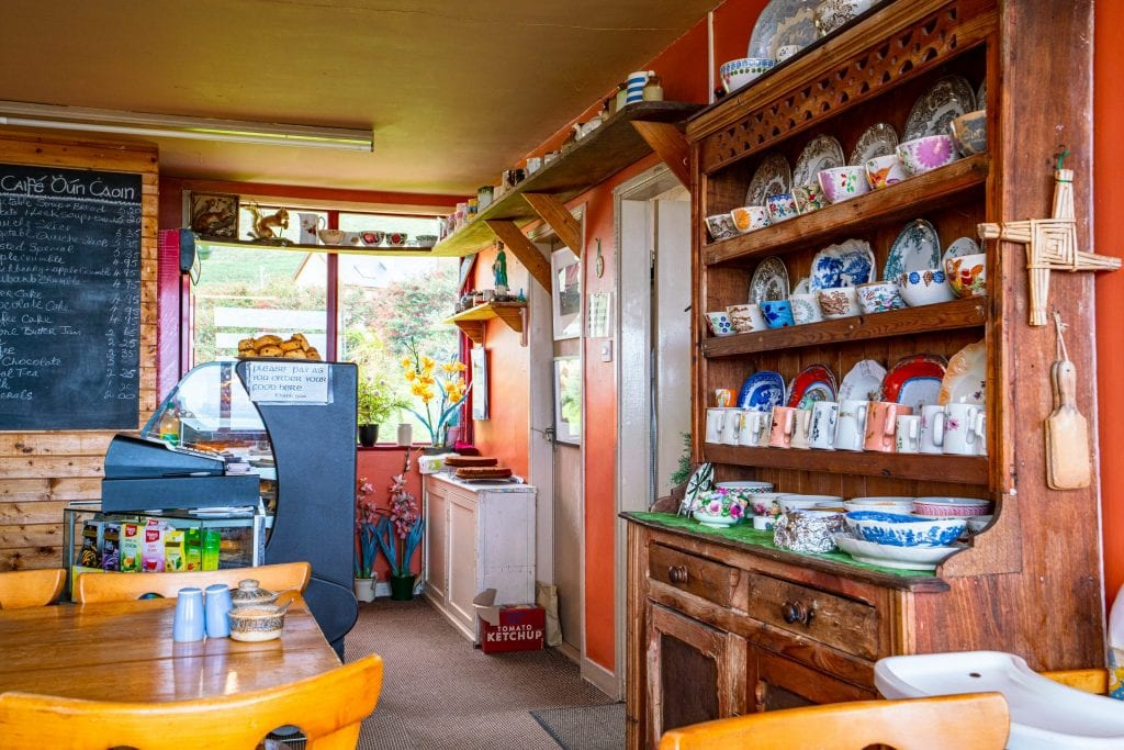 Cozy tearoom in Ireland with a hutch filled with teacups on the right--finding places like this is part of the fun of tracking down what to eat in Ireland
