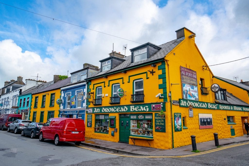 Colorful street in Dingle Ireland with a bright yellow building. Dingle is the starting point for Slea Head Drive.