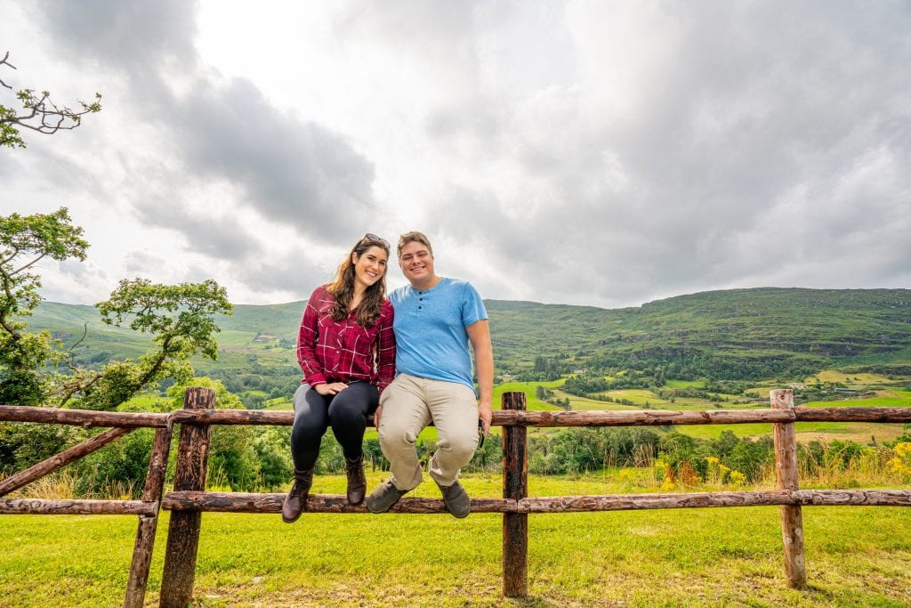 Kate Storm and Jeremy Storm sitting on a split-level fence in Ireland while on an Ireland road trip
