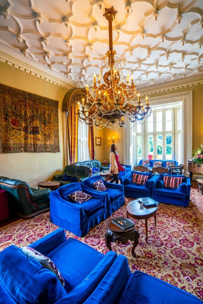 Kate Storm standing in the Library of Belleek Castle County Mayo Ireland, surrounded by blue couches with a chandelier hanging from the ceiling