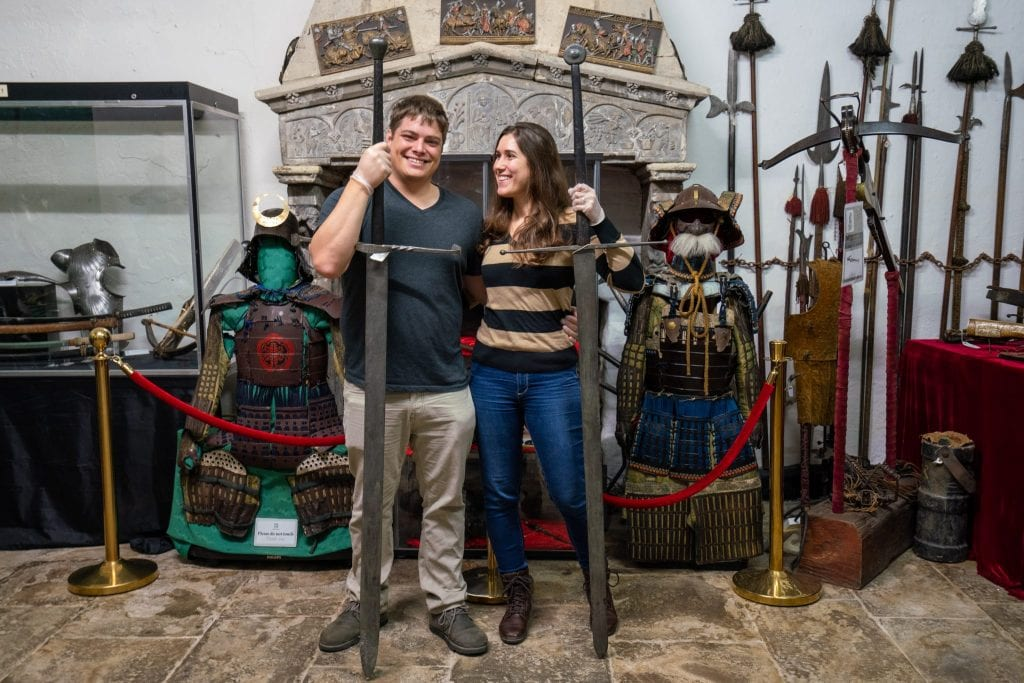 Kate Storm and Jeremy Storm hold tall swords in front of other antique weapons at Belleek Castle in Ireland
