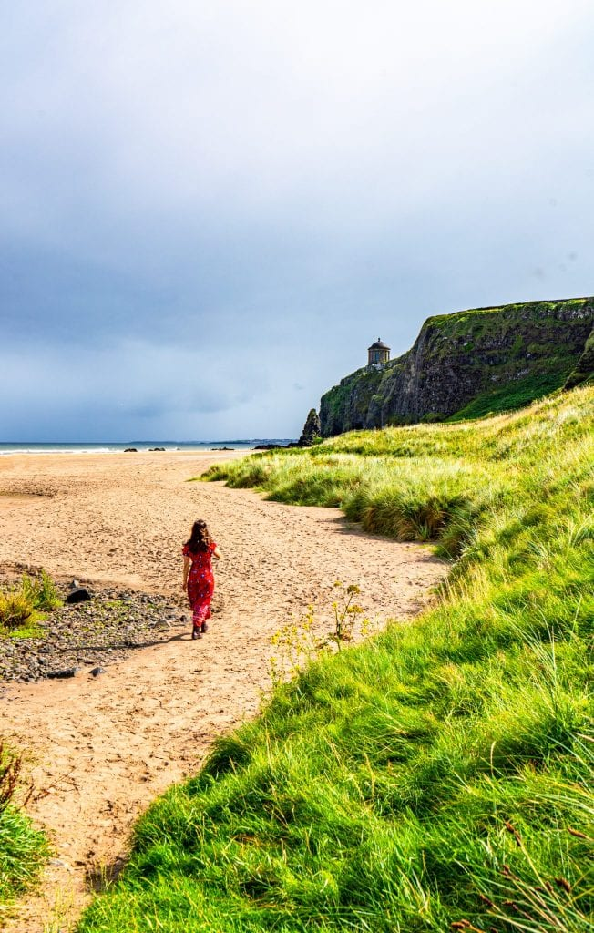 Kate Storm in a red dress on Downhill Beach in Northern Ireland, one of best things to see in Ireland off the beaten path
