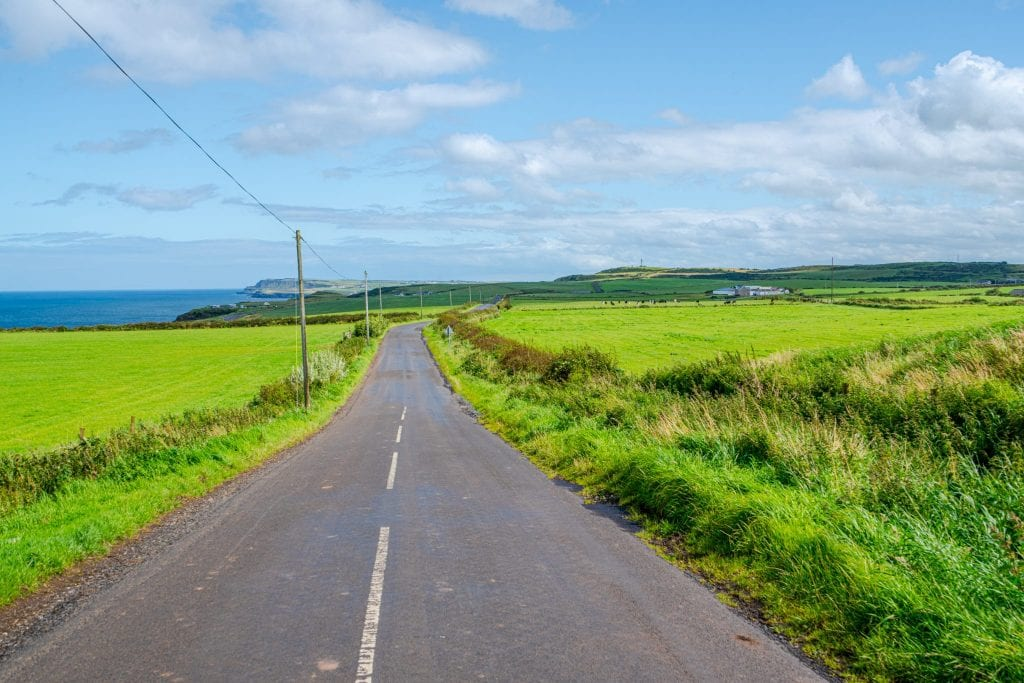 Open road in Northern Ireland with green fields on either side