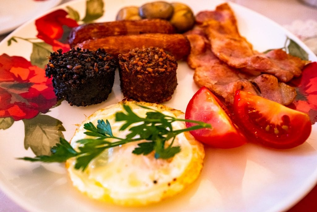 Full Irish breakfast with black and white pudding in the center of the plate--when looking for the best food in Ireland, definitely try both puddings!