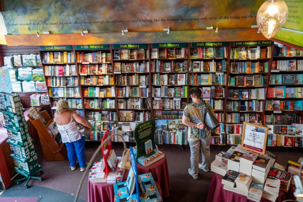 Bookstore in Ireland as shot facing a line of bookcases on the back wall. A few people are browsing at the shelves
