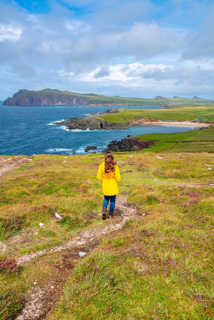 Kate Storm in a yellow raincoat at Dunmore Head Ireland, with the Three Sisters visible in the background