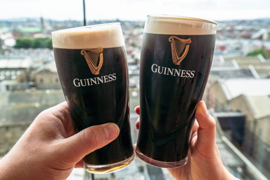 Two pints of Guinness being held up in front of a window at the Guinness Storehouse--definitely pay this spot a visit during your 2 days in Dublin Ireland.