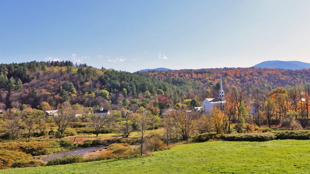 Stowe Vermont from above with fall colors on the trees and a white church on the right side of the photo