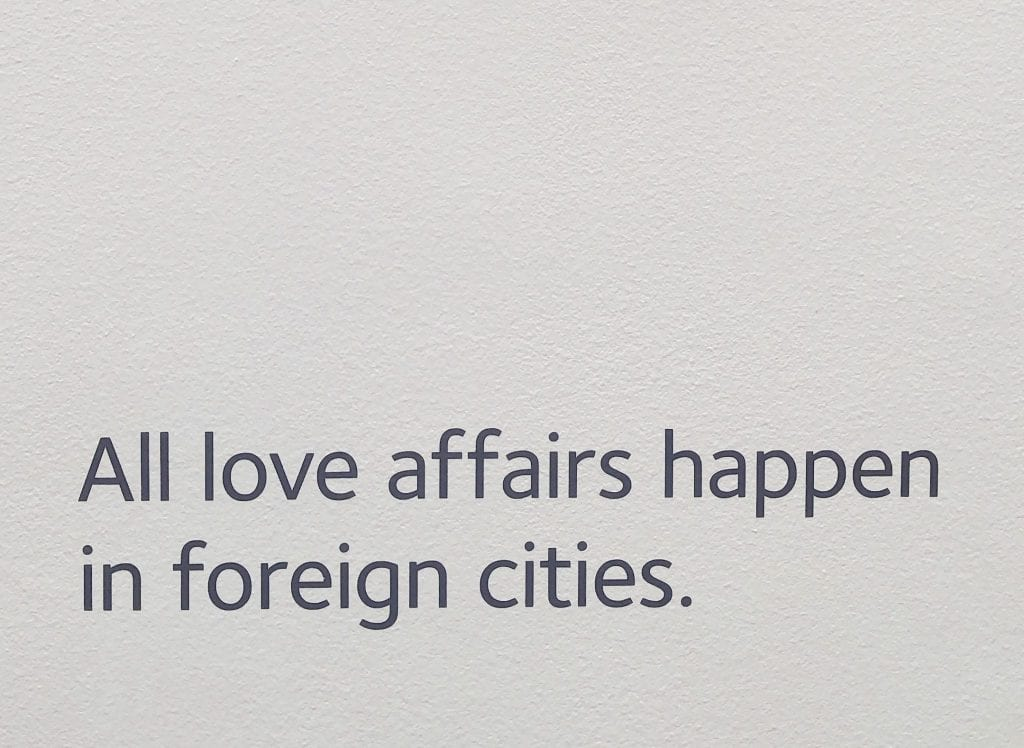 "Photo of white wall in the Museum of Broken Relationships in Zagreb Croatia. Black text reads ""All love affairs happen in foreign cities."""