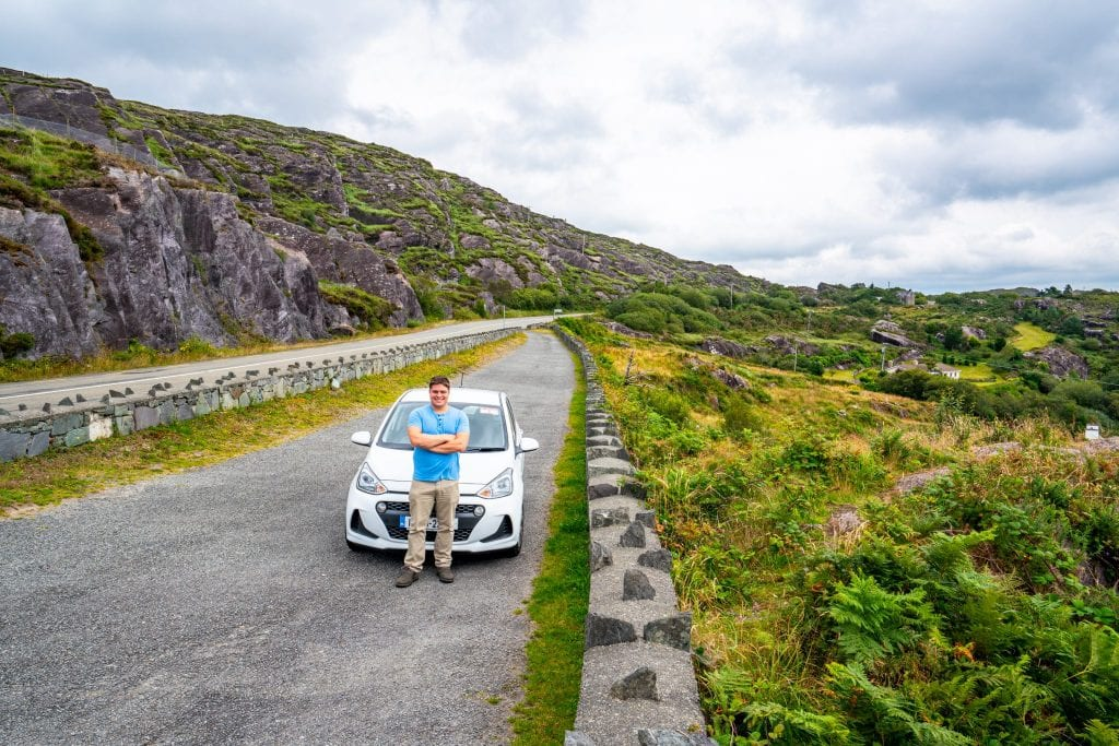 Jeremy Storm with a white rental car on the Ring of Beara during an Ireland road trip
