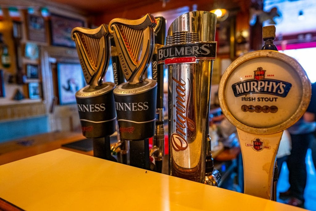 Collection of beer pulls with beer on top in a pub in Ireland