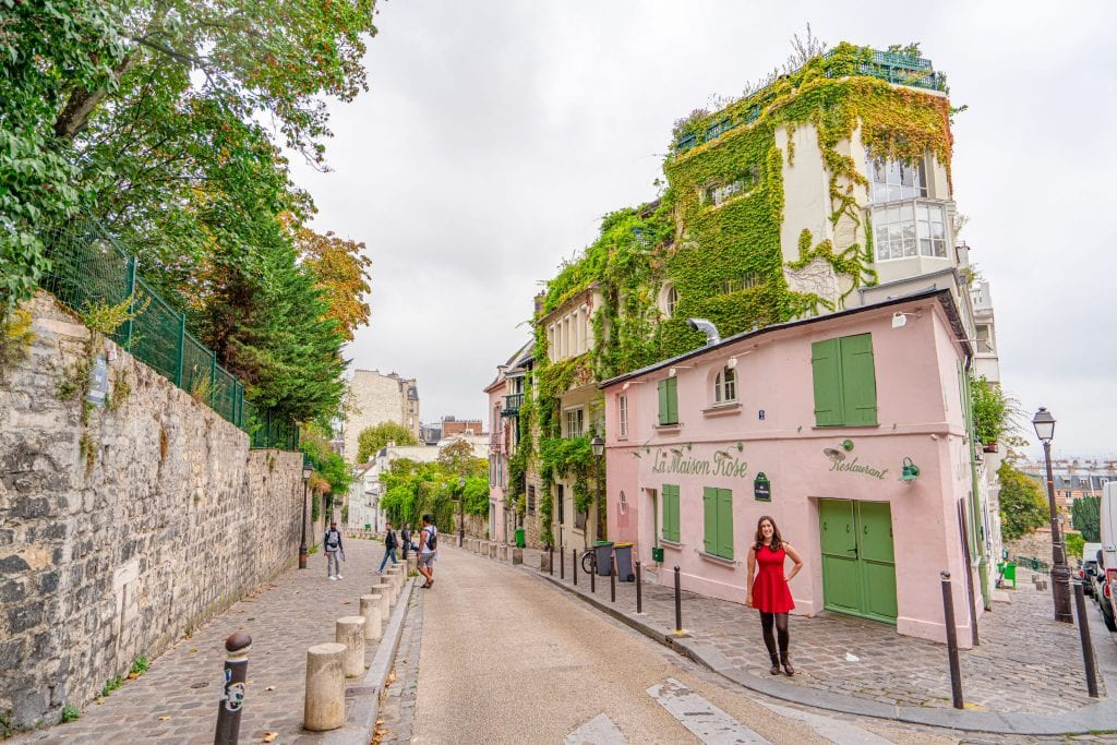 kate storm standing in front of la maison rose, a parisian bucket list sightseeing stop