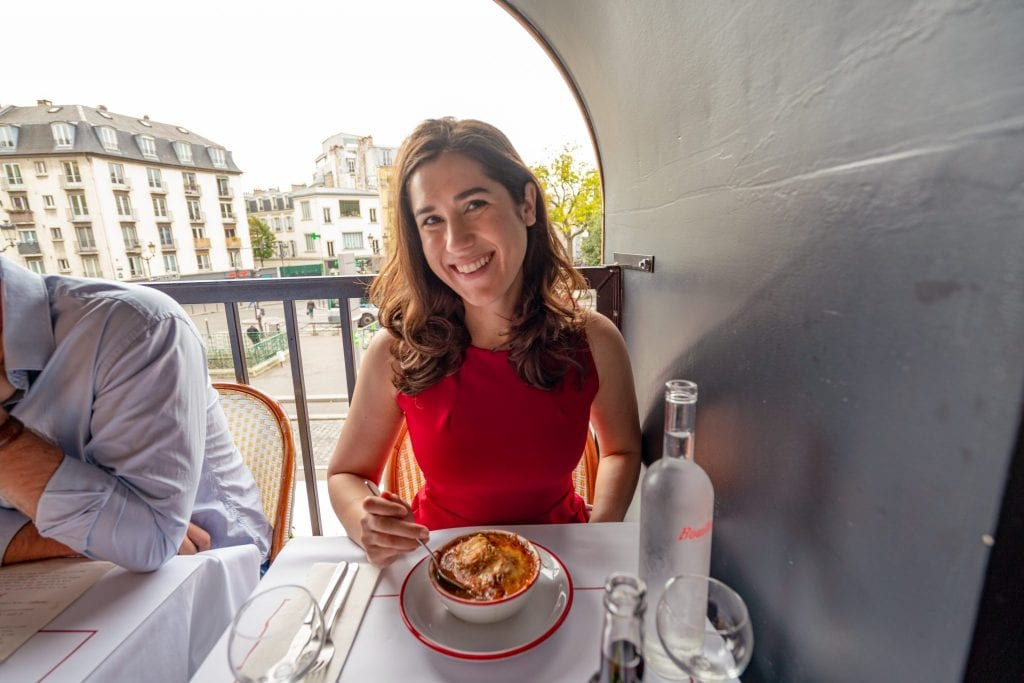 Kate Storm in a red dress with a bowl of French onion soup on the table in front of her--Bouillon Pigalle is a great pick for lunch during your weekend trip to Paris!