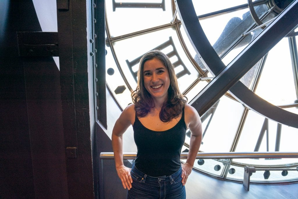 Kate Storm in a black tank stop standing in front of the clock in Musee d'Orsay, an excellent part of any 3 days in Paris France!