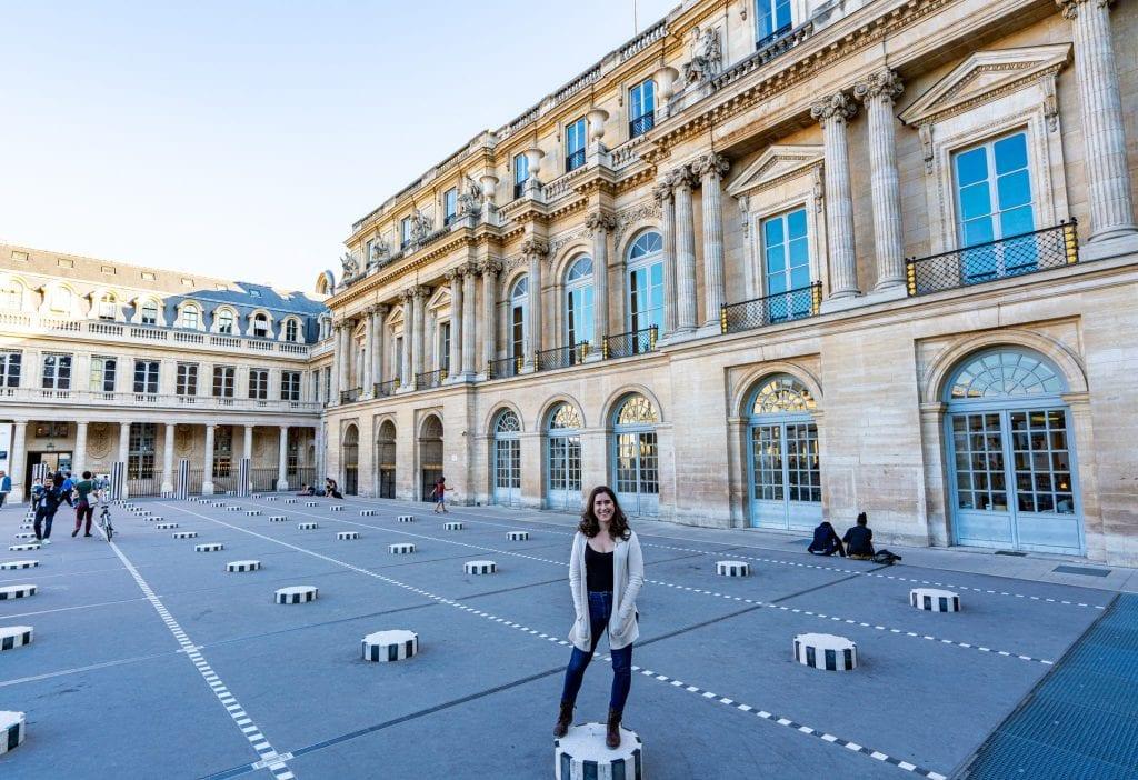 Kate Storm standing amongst the Colonnes de Buren, one of the best photo spots in Paris