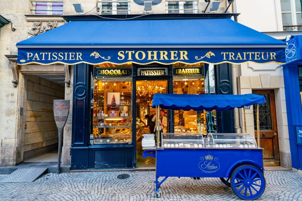 Facade of Patisserie Stohrer in Paris with a blue awning and blue cart out front--definitely stop by here when exploring Paris off the beaten path.