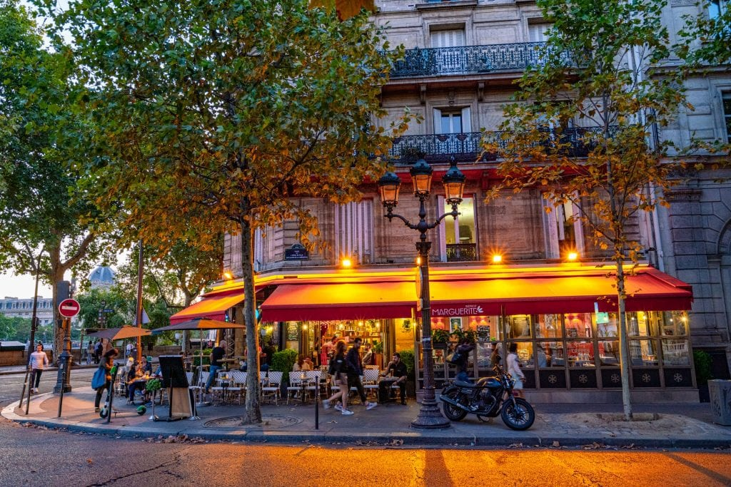 Cozy sidewalk bistro on an evening in Paris, with outdoor tables lit by lamps