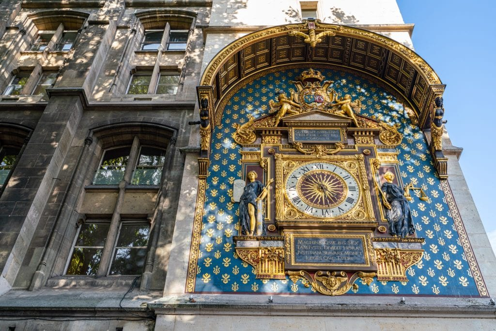 Oldest clock in Paris located on the side of the Conciergerie. The clock is blue and gold, and definitely worth slowing down to take a peek at during any Paris itinerary!