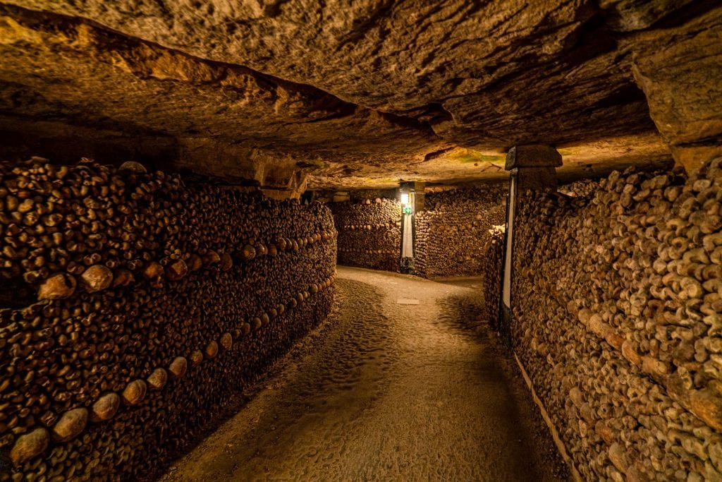Empty path through the Paris catacombs with bones stacked on either side