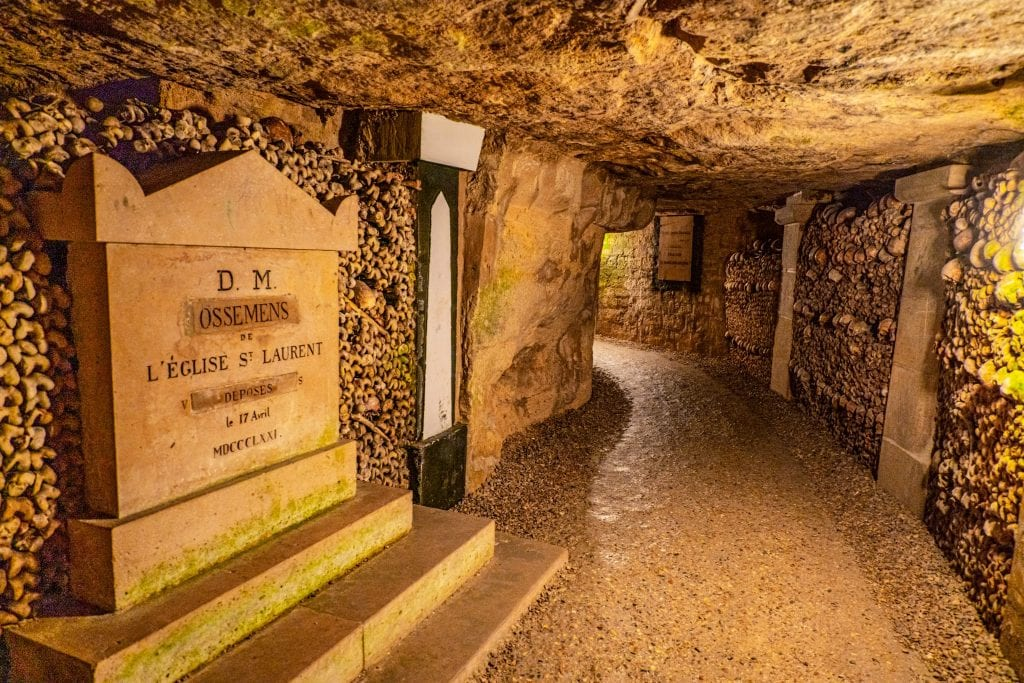Interior of the catacombs in Paris with a gravestone on the left side of the photo