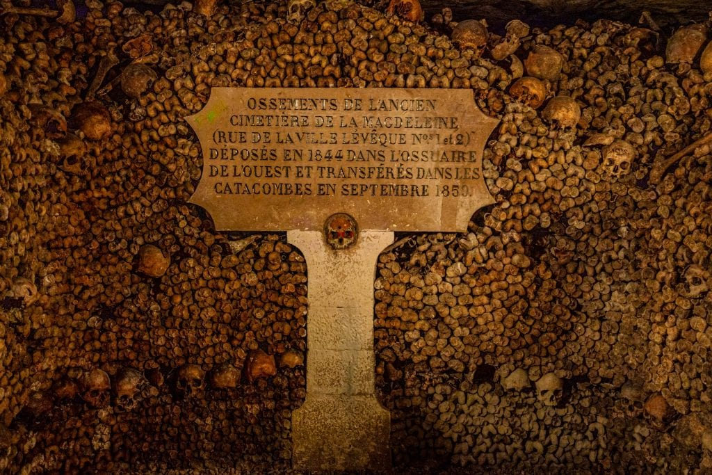Stack of bones with a grave marker in the Paris catacombs