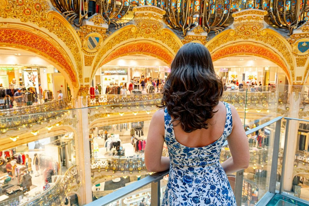 Kate Storm in a blue and white dress looking away from the camera on a skybridge in Galeries Lafayette, one of the best places for photography in Paris