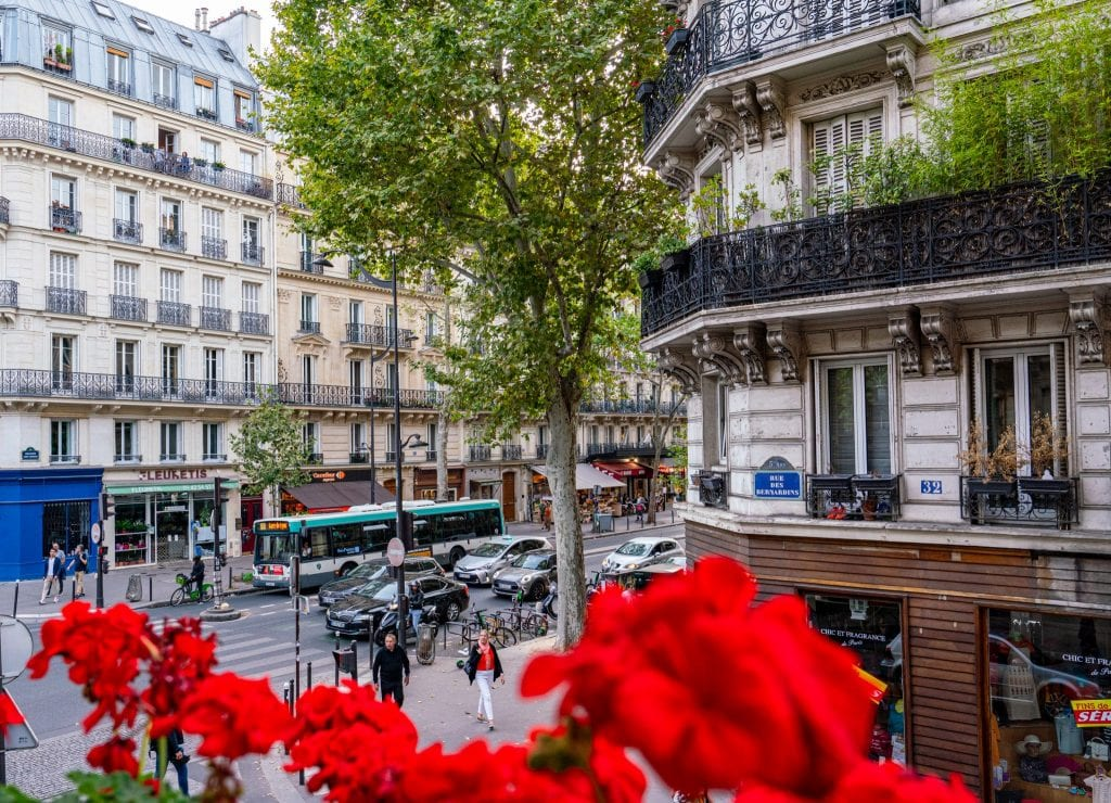 Photo of a Parisian Street looking out a window at Hotel Abbatial Saint Germain with red flowers in the foreground--this is a great pick if you're looking for somewhere to spend your weekend in Paris!