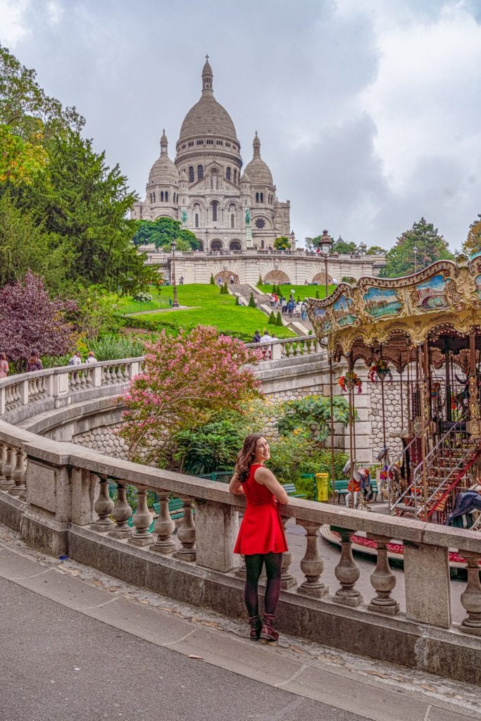 Kate Storm in a red dress standing with a caroseul and Sacre Coeur in the background--this is one of the most instagrammable places in Paris!