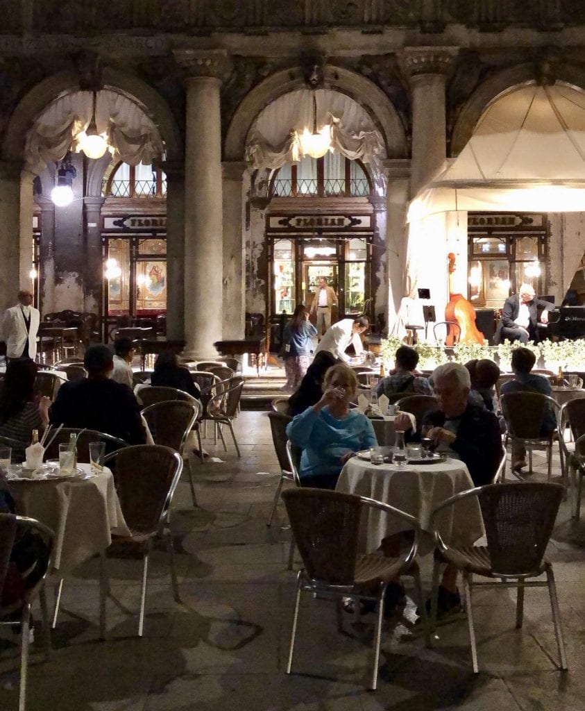 Caffe Florian at night, with patrons sitting at tables in front of the cafe.
