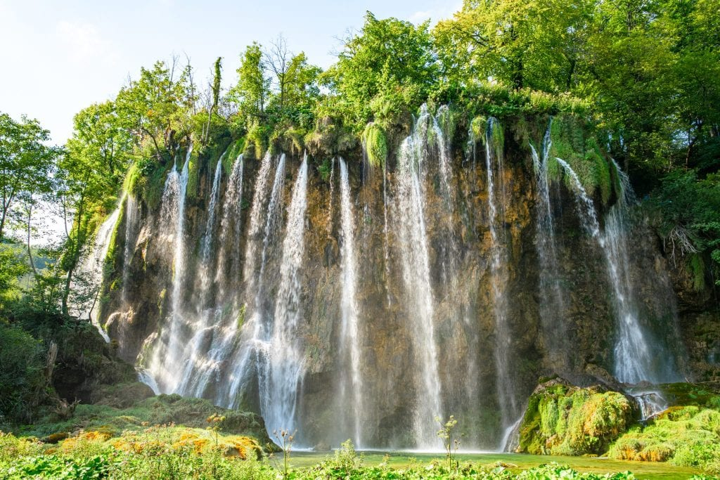 Large waterfall pouring over a broad surface in Plitvice Lakes Park