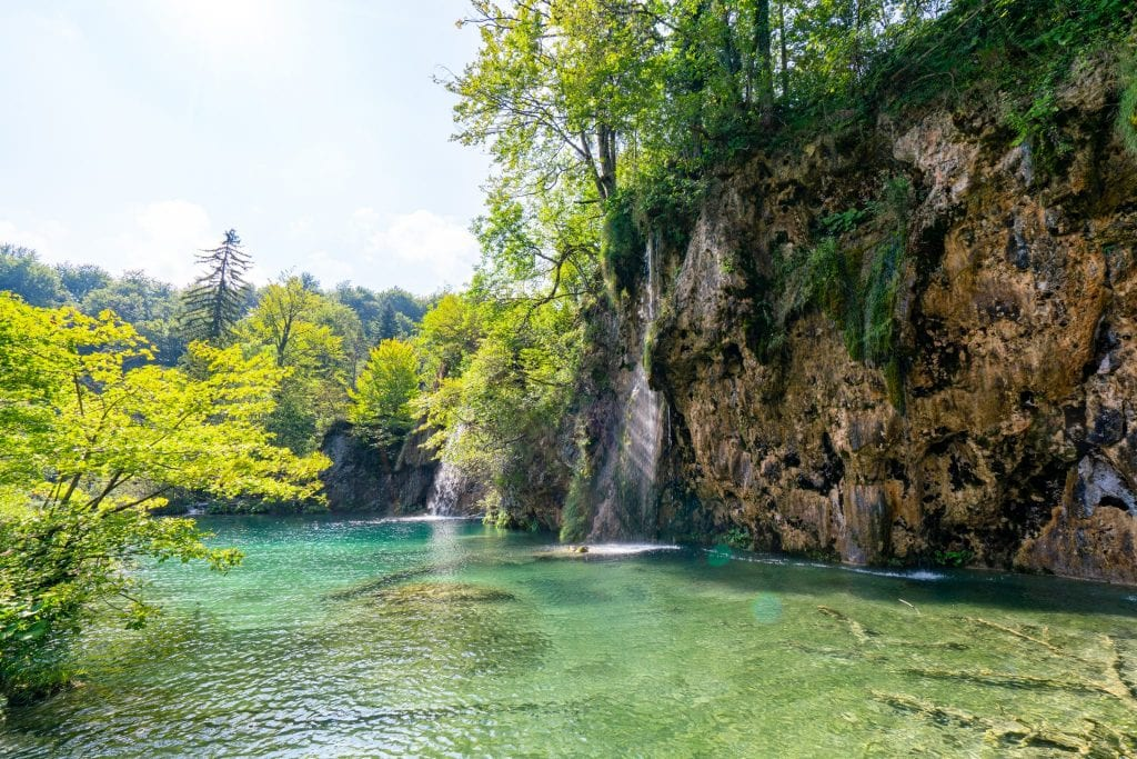 Small waterfall pouring into a shallow lake as seen when visiting Plitvice Lakes National Park Croatia