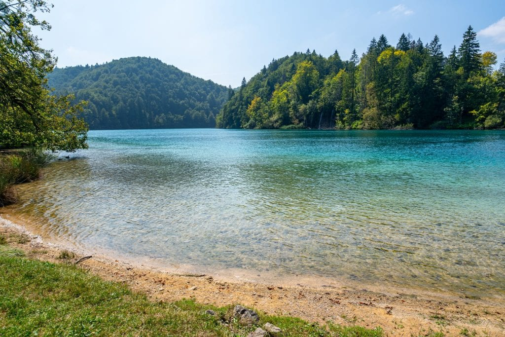 Small beach in Plitvice Lakes National Park Croatia with turquoise lake taking up most of the frame