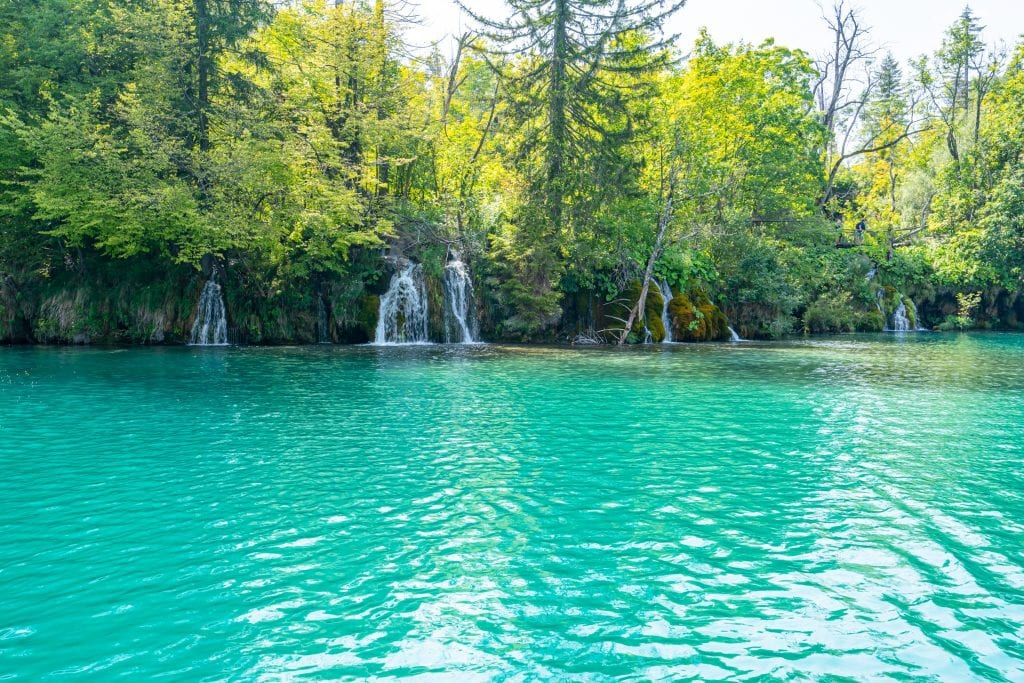 bright turquoise lake with small waterfalls visible in the distance, as seen when visiting Plitvice Lakes Croatia