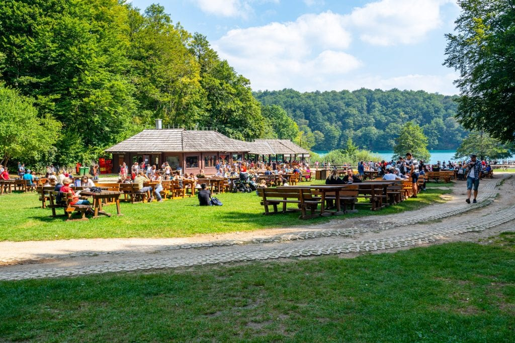 Restaurant inside Plitvice Lakes Park as seen from a distance, with picnic tables visible across the field.
