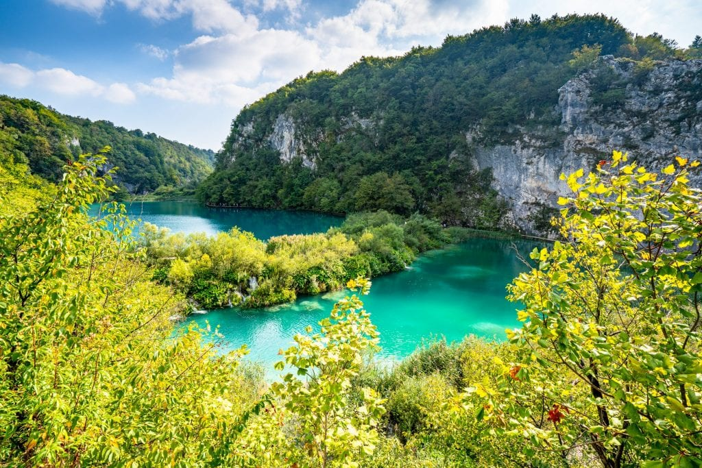 Bright turquoise Plitvice Lakes as seen from above with karst cliffs visible in the distance