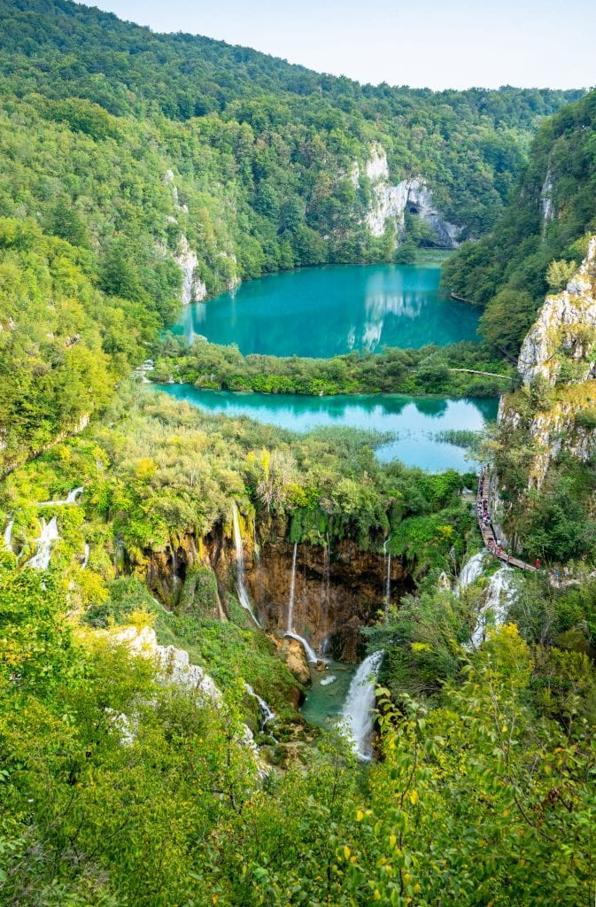 Postcard view of Plitvice Lakes Croatia showing lake and waterfalls seen from above in a vertical image