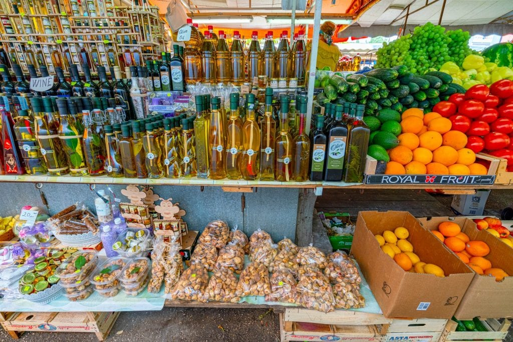 market stall in croatia with fresh fruits and olive oils