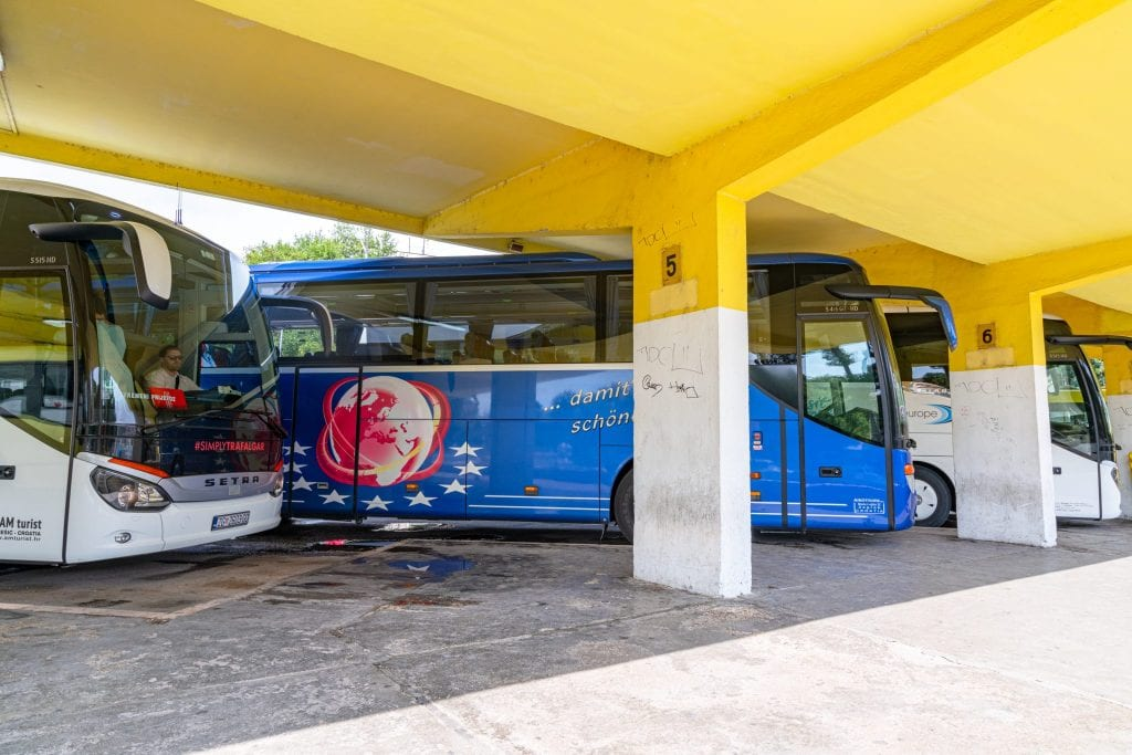 A group of white and blue buses parked under a yellow awning at the bus station in Trogir--riding a bus is almost certainly going to be part of your 10 day Croatia itinerary!