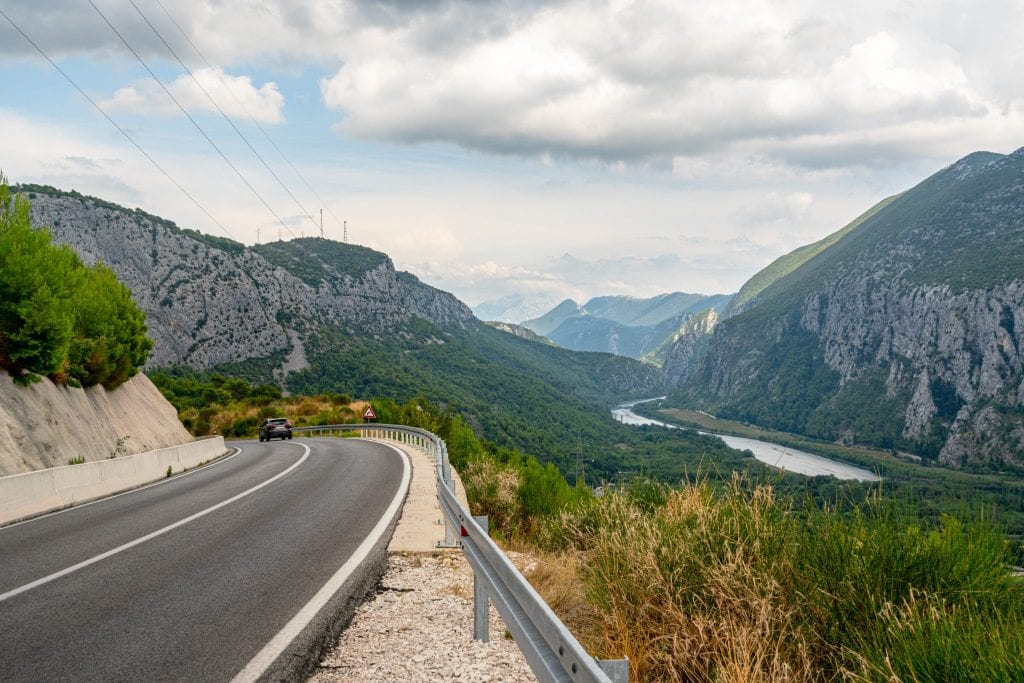 Empty, winding road in Croatia near Omis as seen on a cloudy day with a view of the forest in the background--views like this make a Croatia road trip special!