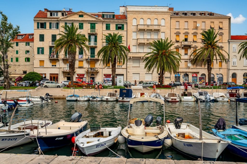 View of Split Croatia Harbor with small boats in the foreground and palm trees in front of buildings in the background