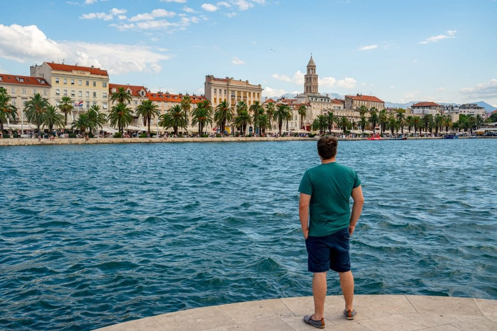 Jeremy Storm in a turquoise shirt standing on the edge of the water, looking away from the camera and toward Split in the distance--whether you visit Split or Dubrovnik, Adriatic views abound!