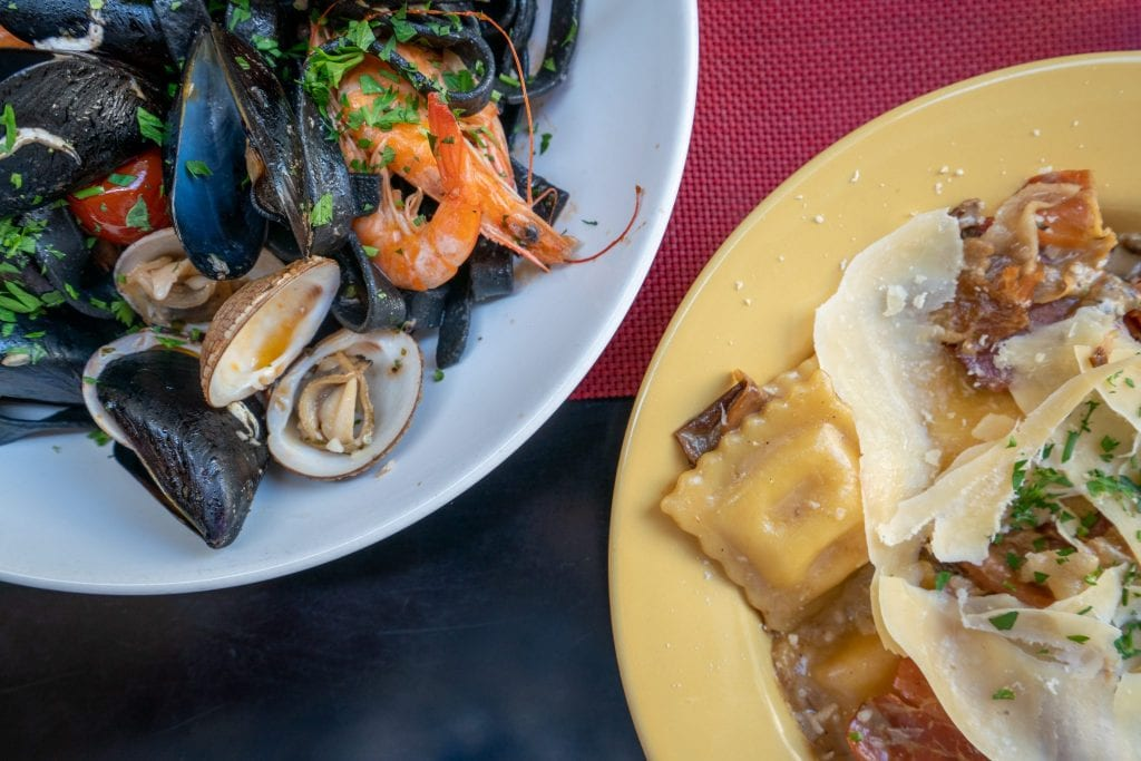 Photo from aboe with plate of mussels on the left and ravioli on the right, taken in Croatia