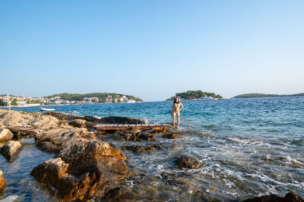 Kate Storm standing on the rocky coastline of Hvar--swimming off the rocks is one of the best things to do in Hvar!