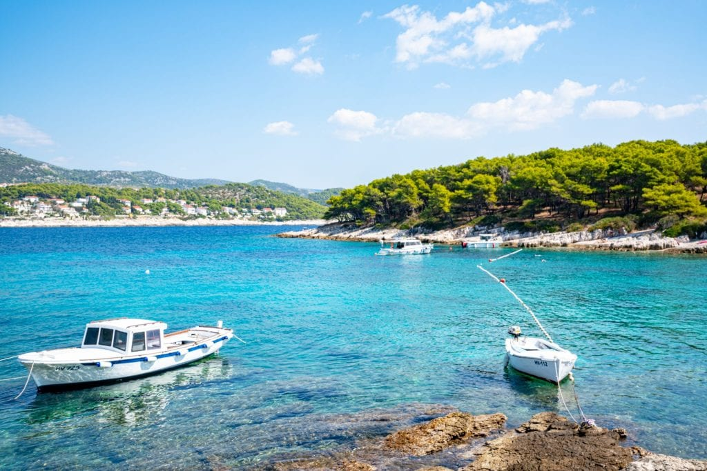 Small boats parked near a rocky shore on the Pakleni Islands, one of the best things to do in Hvar