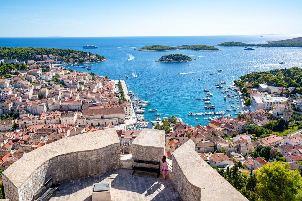 View of Hvar Town from Spanish Fortress with Pakleni islands in background and Kate Storm in a pink dress standing on the fort. Don't miss this view during your 10 day Croatia itinerary!