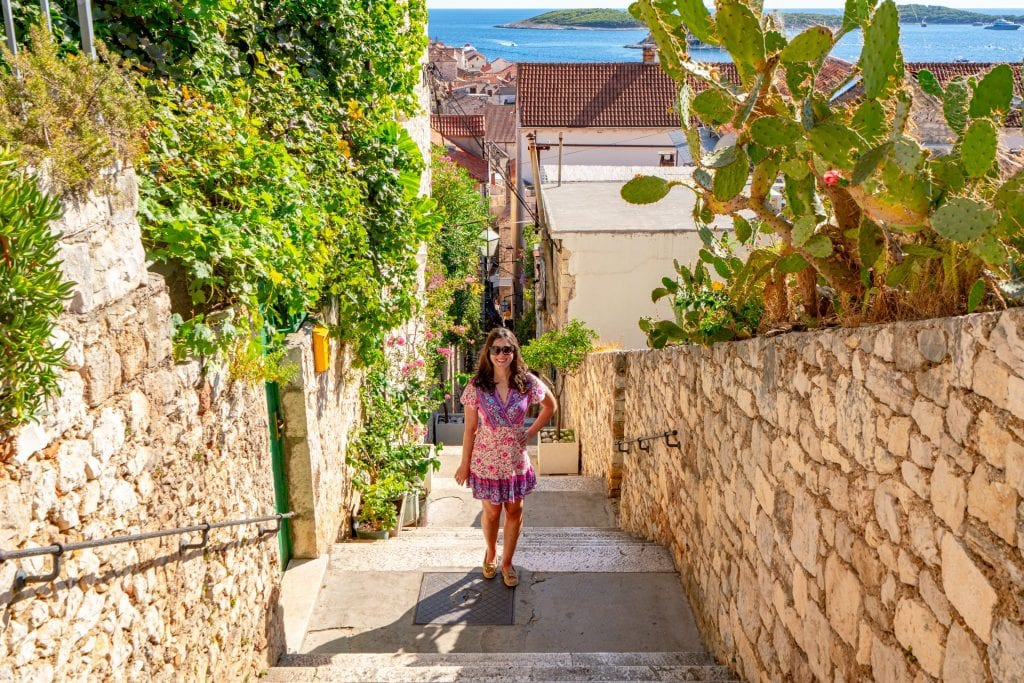 Kate Storm in a pink dress standing on a small stone street in Hvar Croatia