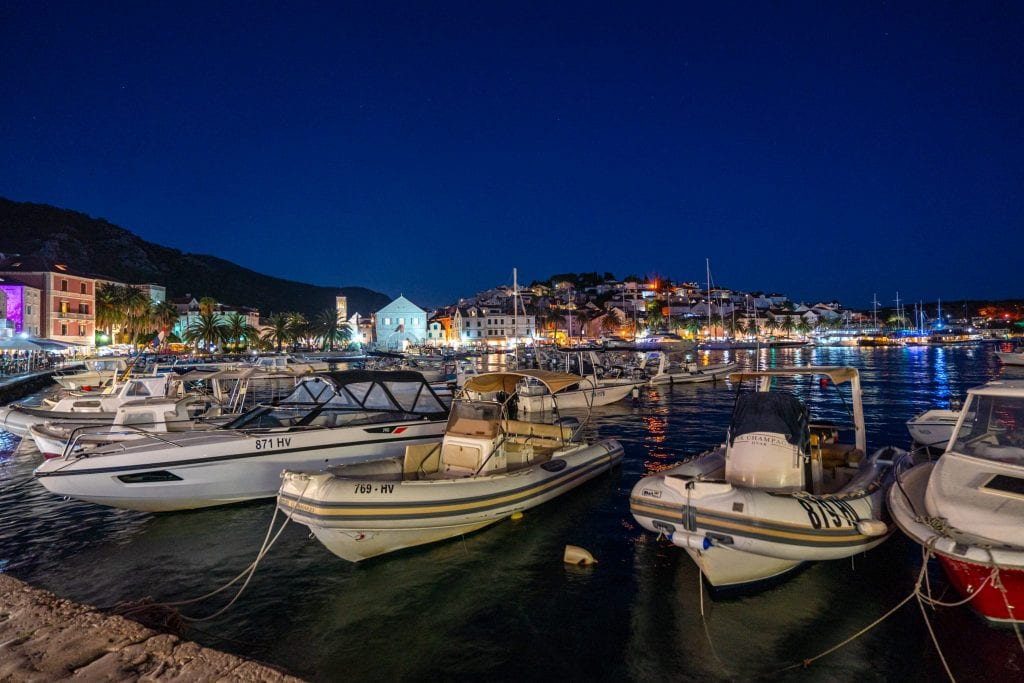 Photo of Hvar's harbor at night with boats in the foreground