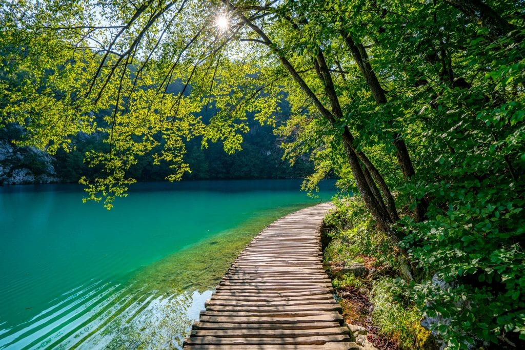 Path made of wooden planks in Plitvice Lakes National Park that is built over a turquoise lake