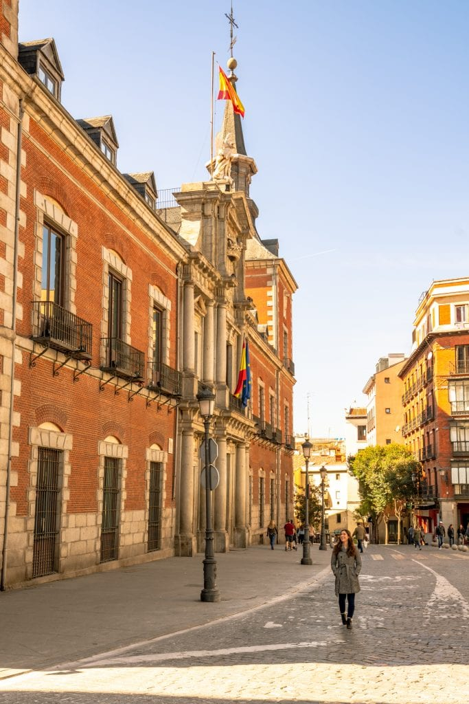 Kate Storm in a gray coat walking down the street in Madrid with a red brick building to her left