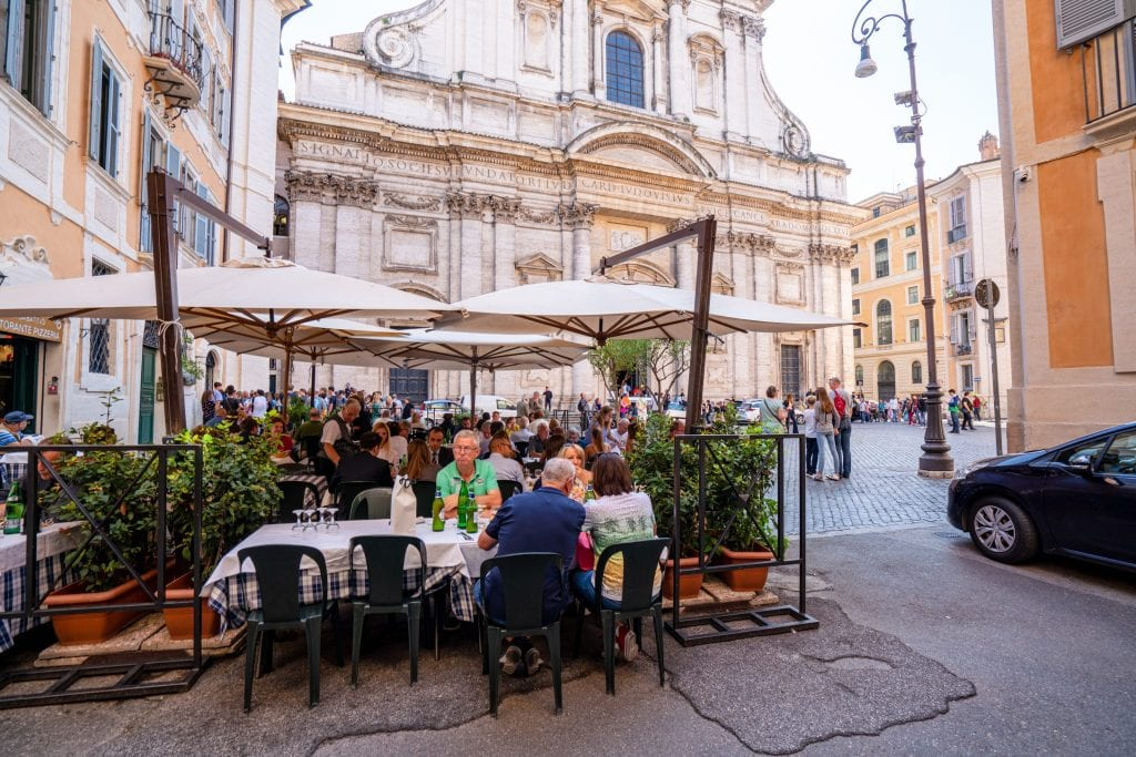 Piazza in Rome with church visible in the background and a restaurant with people dining outside in the foreground. These Rome travel tips will help you find pretty corners like this!